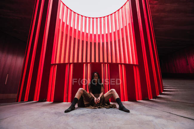 Artista de teatro étnico sentado con las piernas separadas en el suelo cerca de la pared acanalada brillante en el escenario y mirando a la cámara - foto de stock