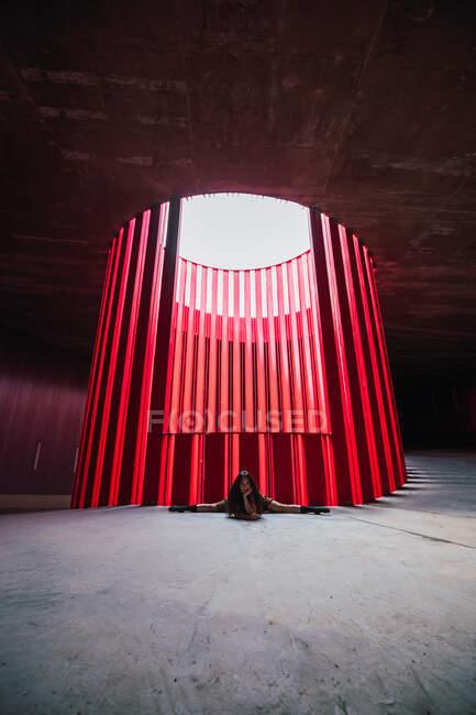 Ballerina flessibile anonima seduta in split mentre si appoggia sulla mano in auditorium luminoso alla luce del giorno — Foto stock
