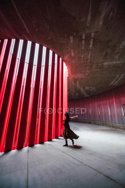 Бічний вид анонімного жіночого театру, який розтягує ногу під час підготовки до виступу на сцені вдень. — стокове фото
