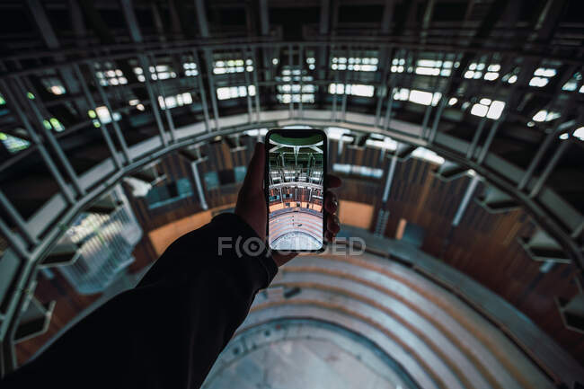 From above of crop anonymous person demonstrating photo of theater interior with stairs on cellphone screen — Stock Photo