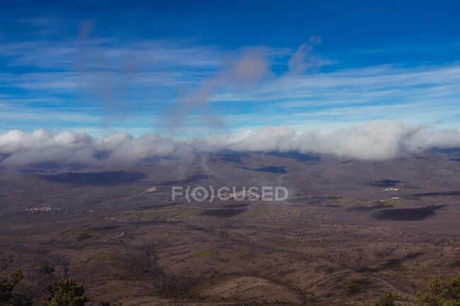 В Іспанії, під ясним блакитним хмарним небом, видніється вид гори з сухим рельєфом. — стокове фото
