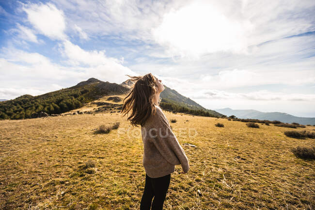 Side view of young gentle female traveler in casual outfit with eyes closed against mount in sunlight in Spain — Stock Photo