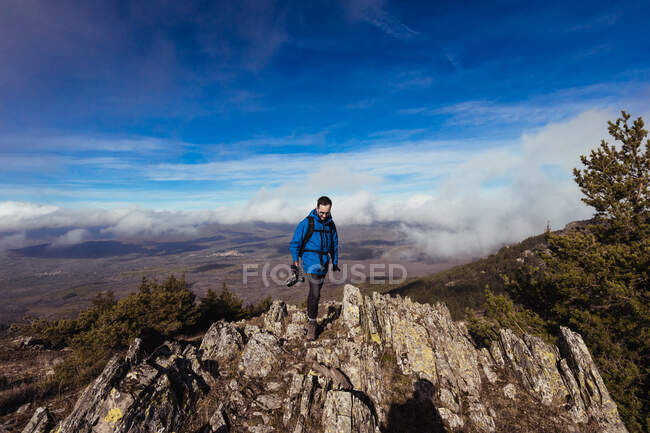 Male traveler in outerwear with photo camera looking down from mount under blue cloudy sky in Spain — Stock Photo