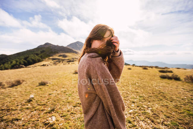 Young gentle female traveler in casual outfit looking at camera against mount in sunlight in Spain — Stock Photo