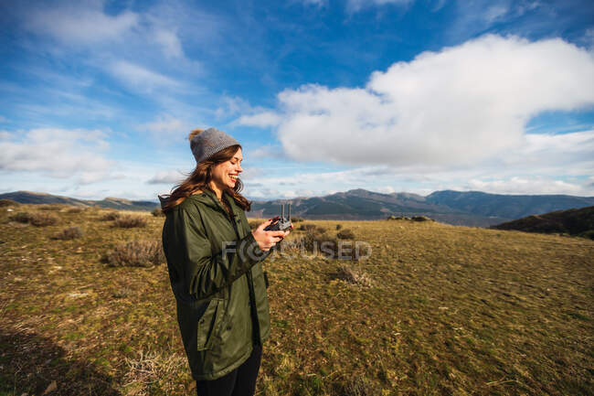 Young female tourist with pouting lips controlling UAV with remote controller while looking away on lawn in Europe — Stock Photo