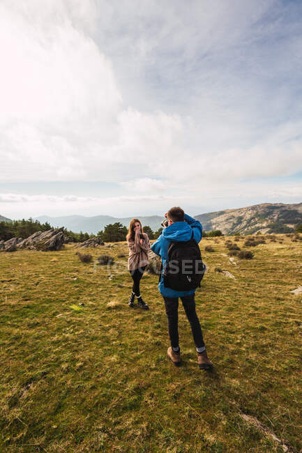 Unrecognizable male trekker taking photo of female partner on camera while standing on lawn against mount under cloudy sky — Stock Photo