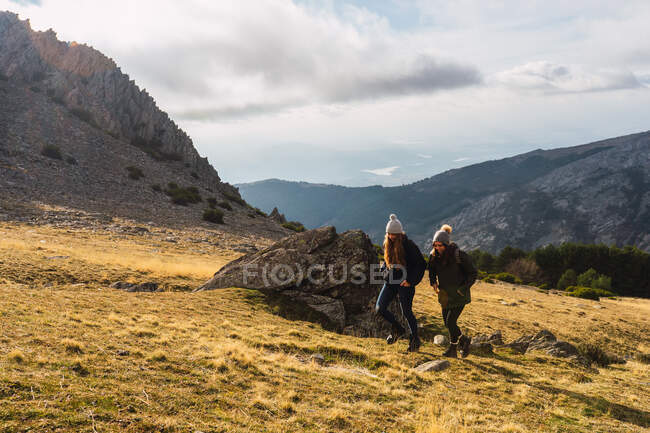 Unrecognizable best female friends in outerwear strolling on mount with grass during trip in Spain — Stock Photo