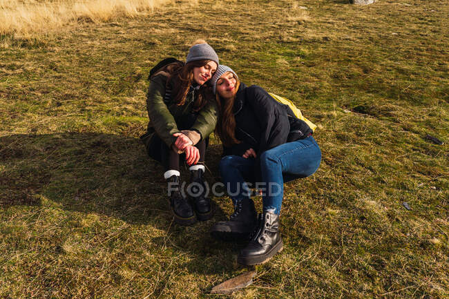 From above of content girlfriends with closed eyes in outerwear sitting close on grass in sunlight — Stock Photo