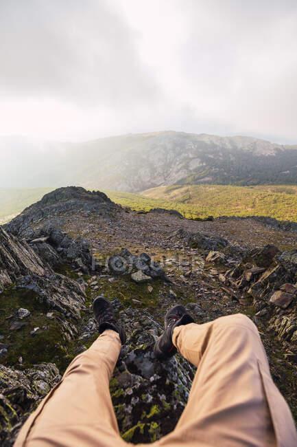 Невідомий турист у повсякденному одязі лежачи на необжитій землі проти гір під час подорожі до Іспанії. — стокове фото