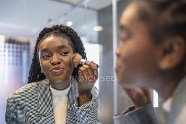 Side view of crop confident young African American lady with long dark hair looking in mirror and applying powder on face with brush in bathroom — Stock Photo