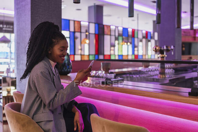 Side view of self assured young African American lady with long curly hair in stylish outfit smiling while sitting at illuminated counter in modern cafe and messaging on smartphone — Stock Photo