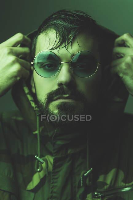 Confiante brutal cara hipster barbudo em casaco com capuz e óculos de sol redondos da moda olhando para a câmera em estúdio com luz verde — Fotografia de Stock
