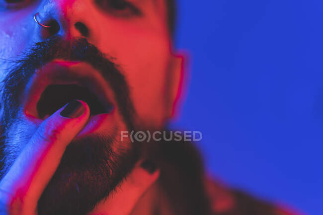 Primo piano di adulto barbuto eccentrico maschio con piercing e verniciato unghie nere toccare le labbra e guardando la fotocamera in studio con luci fluorescenti al neon — Foto stock