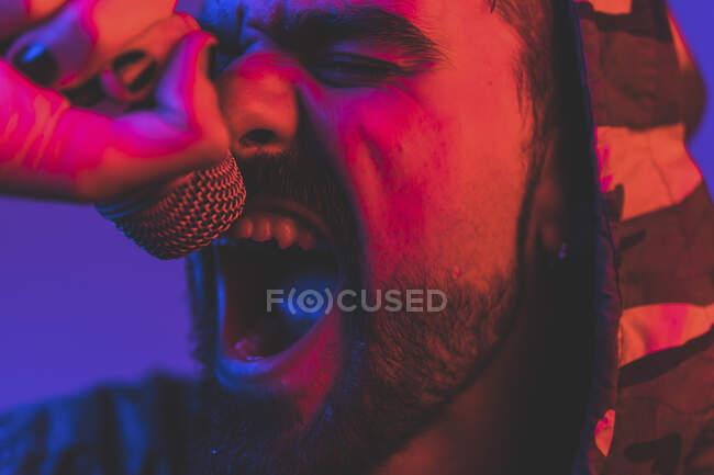 Cantante maschio adulto barbuto in giacca incappucciata che esegue canzone espressiva con microfono durante concerto rock in illuminazione al neon — Foto stock