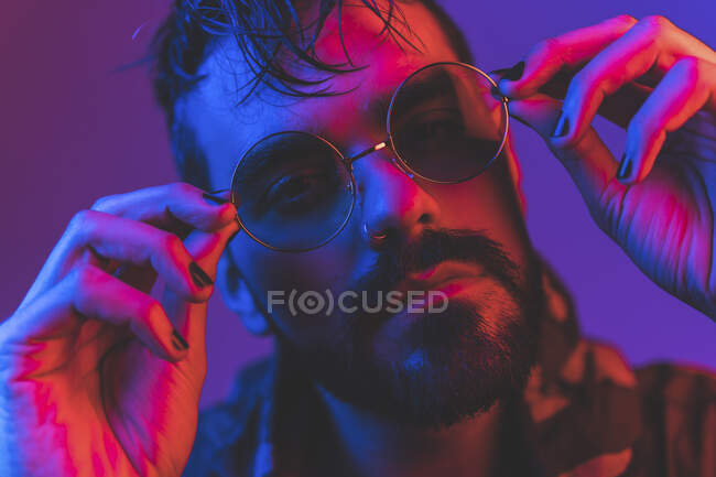 Extravagant adult bearded male with painted nails adjusting trendy round sunglasses and looking at camera in studio with red and purple neon illumination — Stock Photo