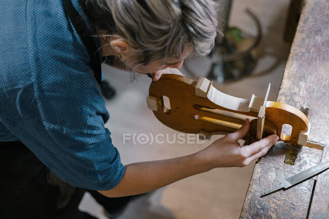 From above female in shirt attaching instrument body to table while crafting violin in professional studio — Stock Photo