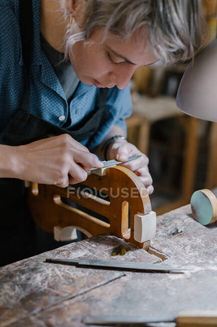 Female artisan in apron carving curve on violin body near lamp during work in professional studio — Stock Photo
