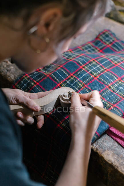 Concentrated woman with gray hair carving ornament on pegbox near lamp while crafting violin in workshop — Stock Photo
