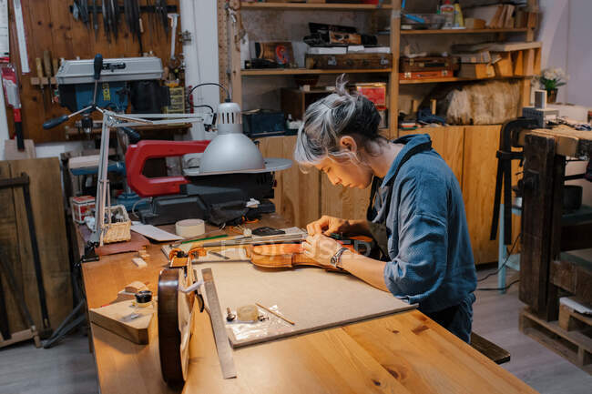 Side view of female artisan attaching strings to violin under lamp while sitting at table and working in workshop — Stock Photo