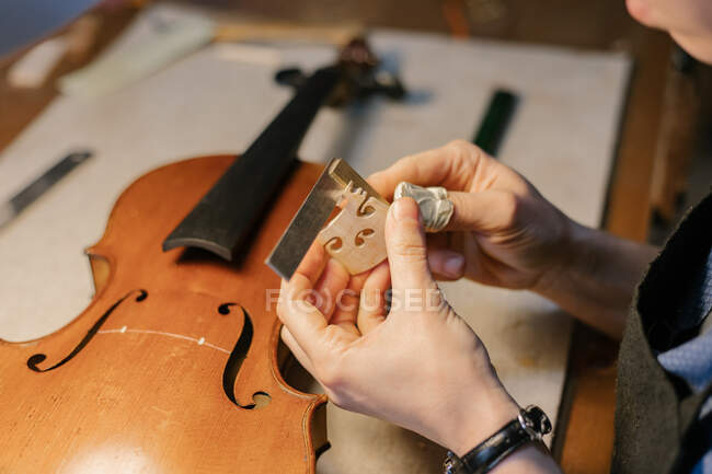 High angle of anonymous woman with bandaged thumb carving wooden ornament while crafting violin on table in workshop — Stock Photo