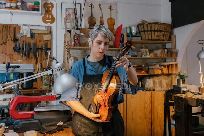 Craftswoman in apron inspecting handmade violin while standing near workbench and shelves in professional studio — Stock Photo