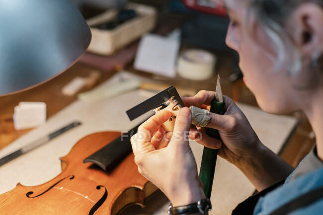From above female artisan cutting wooden decoration for handmade violin while working in workshop — Stock Photo