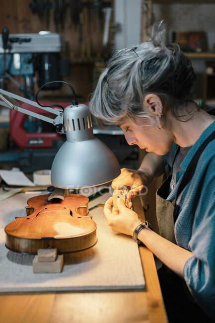 Боковой вид женщин-мастериц, резающих деревянные украшения для скрипки ручной работы во время работы в мастерской — стоковое фото