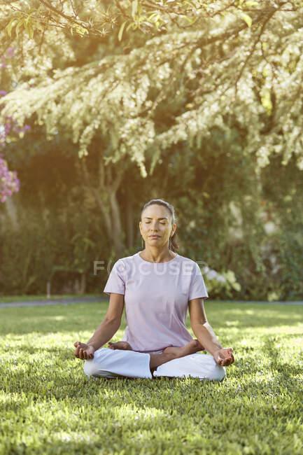 Сосредоточенная гибкая женщина в спортивной одежде сидит на позе лотоса, практикуя йогу на коврике в саду с закрытыми глазами — стоковое фото