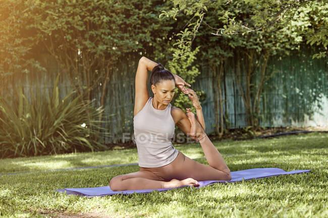 Взрослая гибкая женщина сидит в позе Эка-пады Раджакапотасаны, практикуя йогу и глядя вниз в летнем парке — стоковое фото
