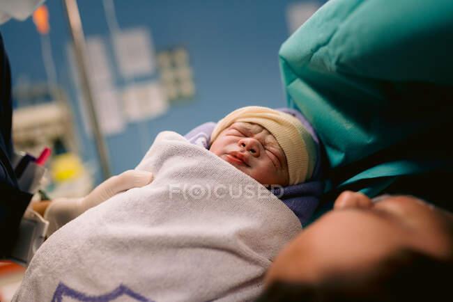 Cosecha enfermera anónima dando bebé recién nacido envuelto en manta a mamá acostada en la cama después del parto en el hospital - foto de stock