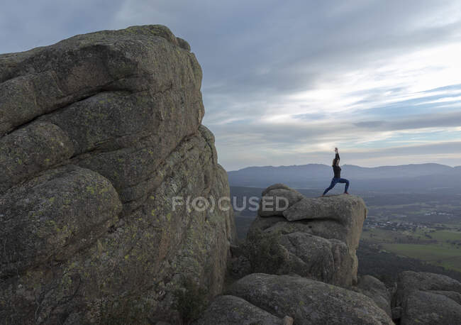 Side view of unrecognizable female standing on top of rocky mountain and doing Warrior one pose during sunset — Stock Photo