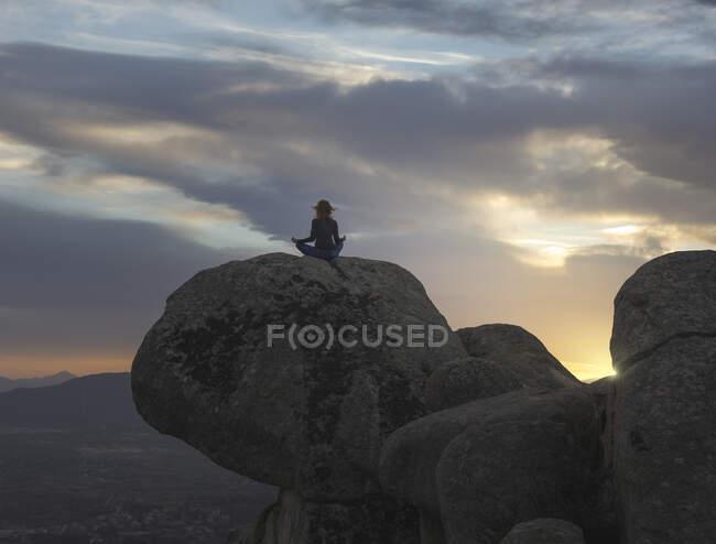Задний вид неузнаваемой спокойной женщины, выполняющей упражнения йоги, практикующей медиацию на каменистой земле на ярком закате — стоковое фото
