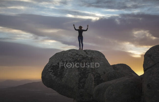 Back view of unrecognizable female standing on top of rocky mountain and doing Mountain pose during sunset — Stock Photo