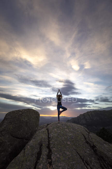 Back view of unrecognizable female standing on top of rocky mountain and doing Tree with Arms Up pose during sunset — Stock Photo