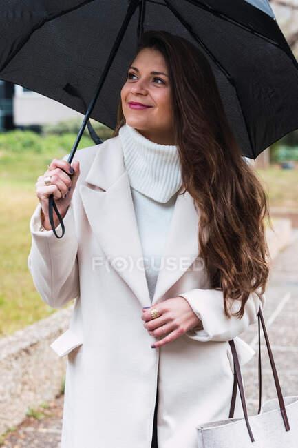 Optimistische erwachsene langhaarige Frau in stylischem weißen Pullover und Mantel, die schwarzen Regenschirm und Handtasche trägt und wegschaut, während sie an einem Frühlingstag im Park spaziert — Stockfoto