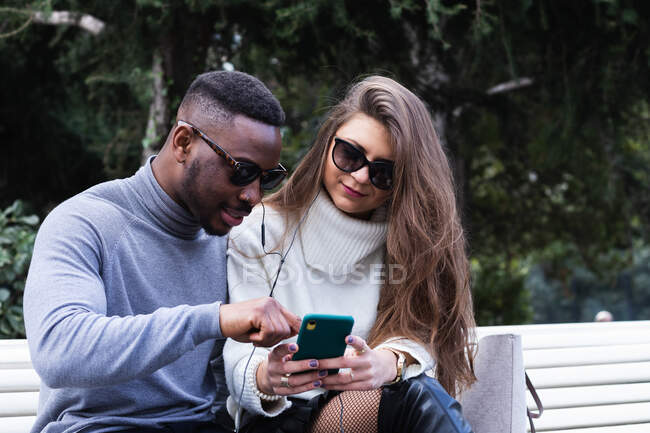 Side view of content adult multiracial couple in love listening music on mobile phone while spending time together in park — Stock Photo