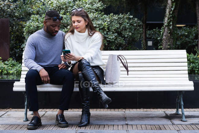 Content adult multiracial couple in love listening music on mobile phone while spending time together in park — Stock Photo