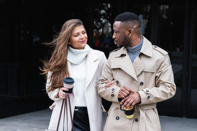 Весела багаторасова пара дорослих у модних плащах з чашками кави, що стоять разом на брукованій міській вулиці. — стокове фото