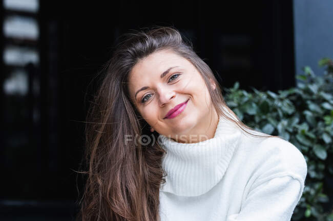 Charming elegant adult long haired brunette with white sweater smiling happily while resting near green bushes in park — Stock Photo