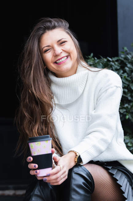 Affascinante donna adulta sognante con tazza di caffè caldo in mano guardando la fotocamera e sorridendo mentre si gode il tempo libero nel parco — Foto stock