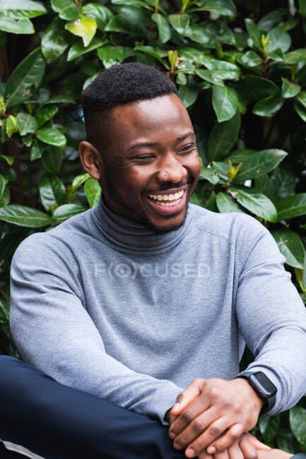 Happy adult African American male in stylish casual wear and wristwatch looking away while sitting against green foliage in park — Stock Photo