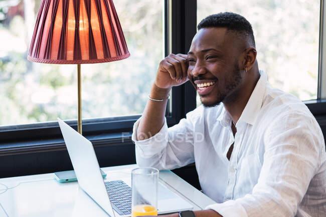 Блаженний афроамериканець, який віддалено користується ноутбуком, сидячи за столом зі склянкою соку в затишному кафе. — стокове фото