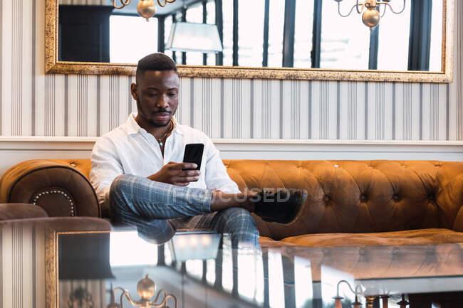 Серьезный молодой афроамериканец в стильной одежде сидит на диване и читает новости по мобильному телефону, отдыхая в стильной гостиной с элегантным дизайном интерьера — стоковое фото