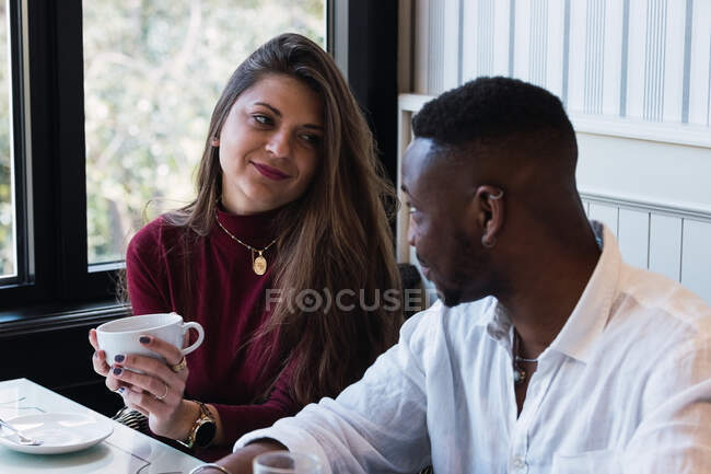 Happy woman with cup of hot drink enjoying pleasant conversation with black boyfriend while having breakfast together in cozy cafe — Stock Photo