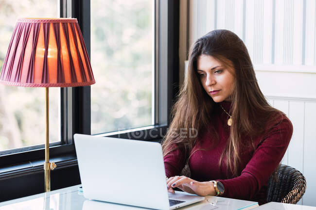 Serious young female freelancer sitting at table near window and using laptop while working remotely in cozy cafe — Stock Photo