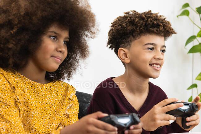 Щасливі етнічні брати і сестри в повсякденному одязі грають цікаву відеогру з гамепадами, сидячи разом на дивані у світлій вітальні. — стокове фото