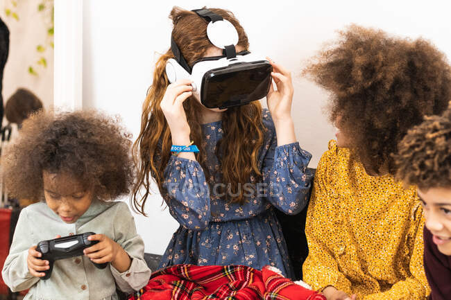 Crop anonymous multiethnic glad friends in VR headset with video game console having fun in house — Stock Photo
