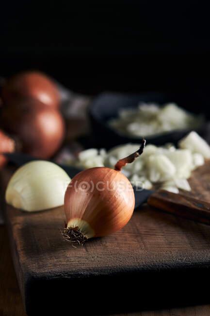 Tigela rústica com pedaços de cebola cortada colocados perto de faca na mesa de madeira na cozinha — Fotografia de Stock