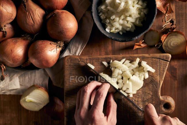 Vista superior de la persona anónima picando cebolla fresca en la tabla de cortar madera mientras cocina la cena - foto de stock
