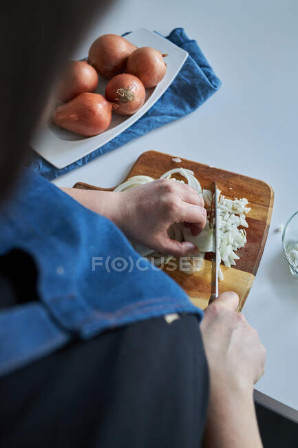 Crop woman in apron chopping raw onion on cutting board on table in kitchen at home — Stock Photo